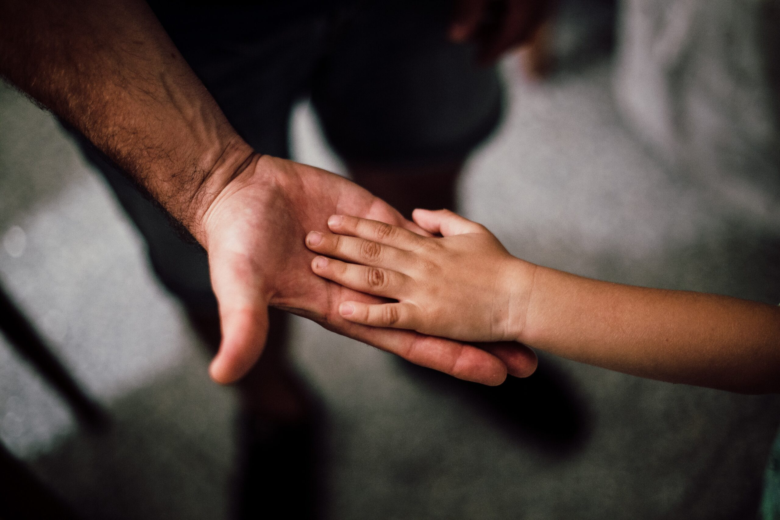 Child putting hand in father's palm